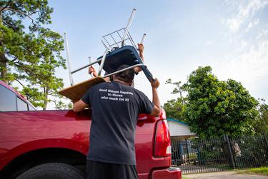 Jesus Sanchez, math instructor at Raul Yzaguirre School for Success, helps load chairs and desks into vehicles during the Drive-Thru Student School Supply Giveaway in Houston on Aug. 22, 2020.