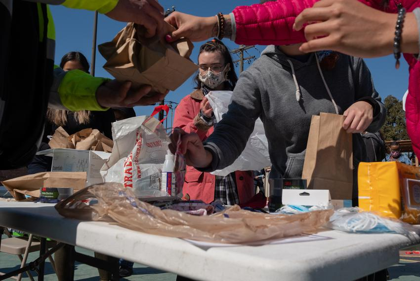 Volunteer Kaede Polkinghorne, center, helps a team of volunteers prepare masks at Kelly Garden at a supply distribution even…