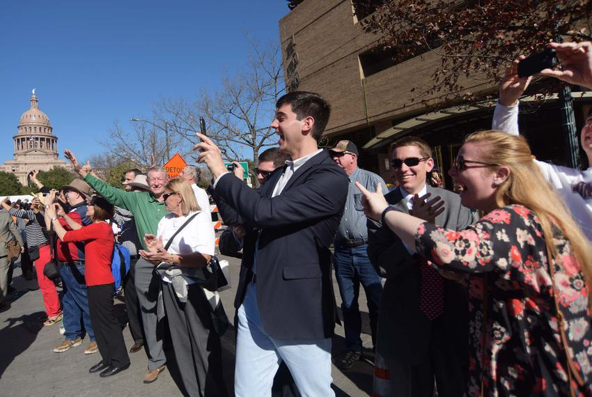 Onlookers wave and take pictures as the inaugural parade makes its way toward the Capitol.