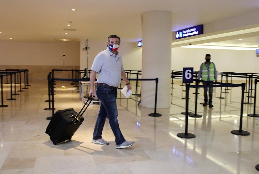 U.S. Sen. Ted Cruz, R-Texas, carries his luggage at the Cancun International Airport before boarding his plane back to the U…
