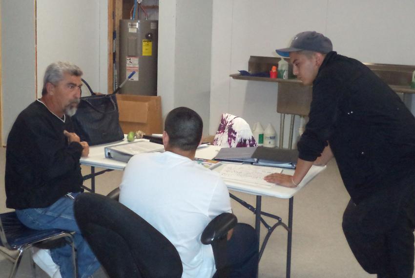 Bruce Ballou, left, and Jose Luis Perez tutor a teenager participating in the alternative education program in Maverick Coun…