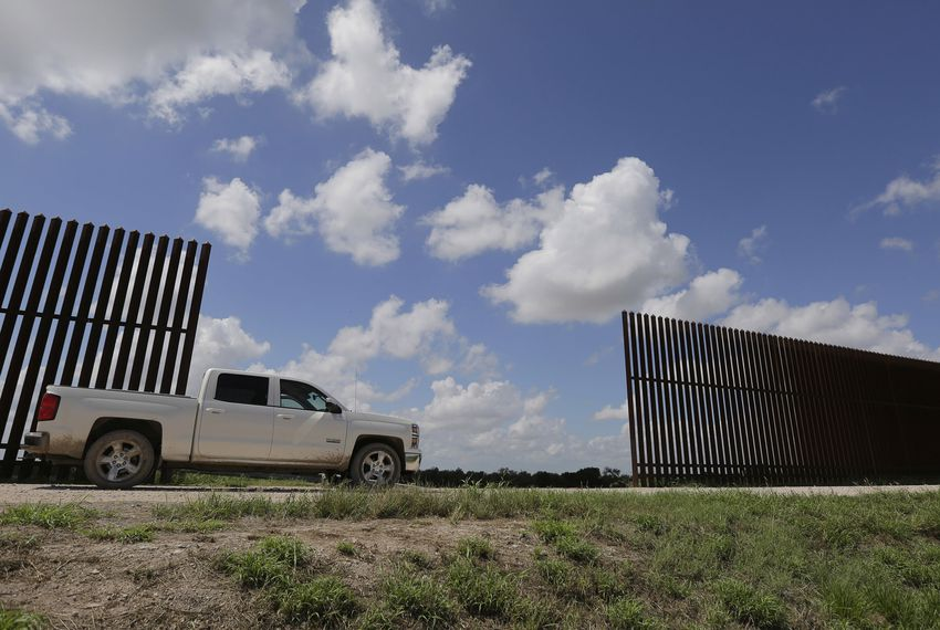 A farmer passes along a border fence that divides his property in Mission on Sept. 15, 2015.