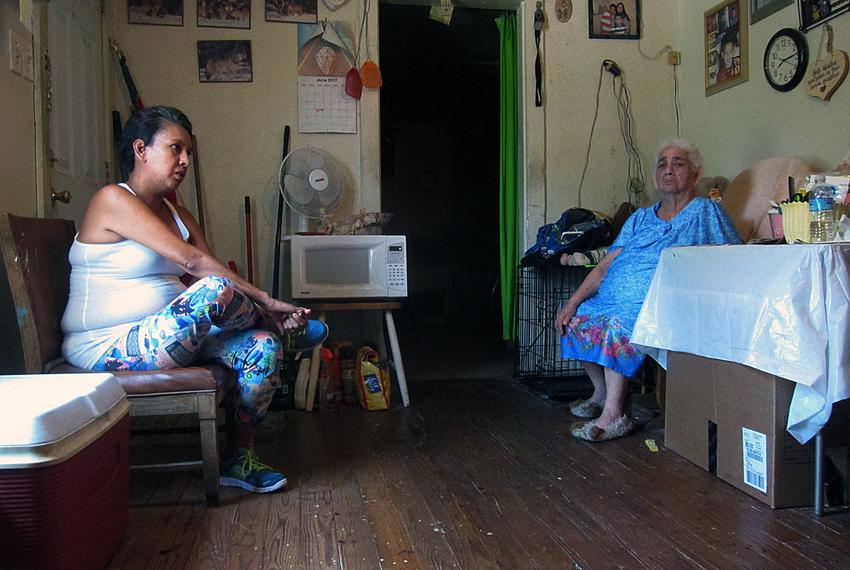 Noemi Pina, 43, and her mother Juana Rosas, 81, sit in their West Dallas living room. They are among scores of residents w...