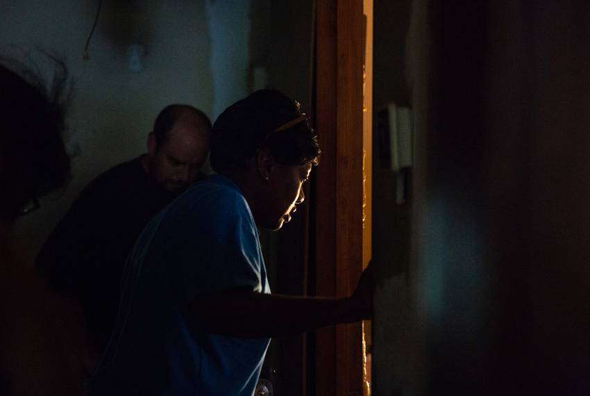 Charla Gilliam, specialist at Adult Protective Services, peers at her client through the doorway during a in-home visit of...