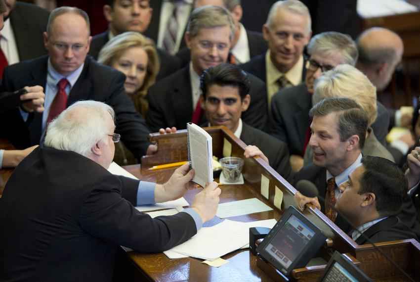 House Parliamentarian Chris Griesel shows the rule book to a group of House members including Rep. David Simpson, R-Longvi...