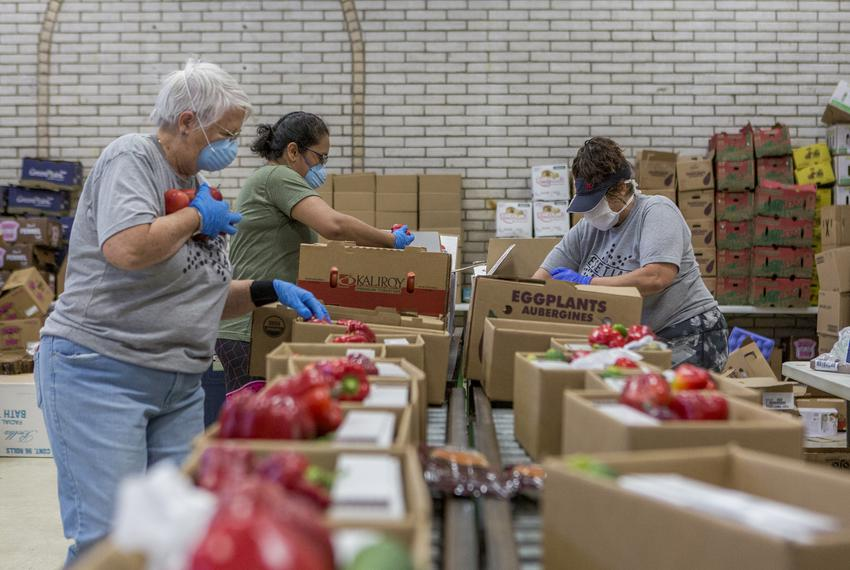 Volunteers Christy Minjarez, Sandy Grace and Yvonne Mendoza prepare boxes of food at the Kelly Memorial Food Pantry in Centr…