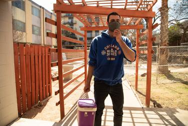 Jack Considine carries a bucket of water collected from an out-of-use pool back to his apartment in Central Austin on Feb. 24, 2021. He uses that unsanitary water to refill his toilet.