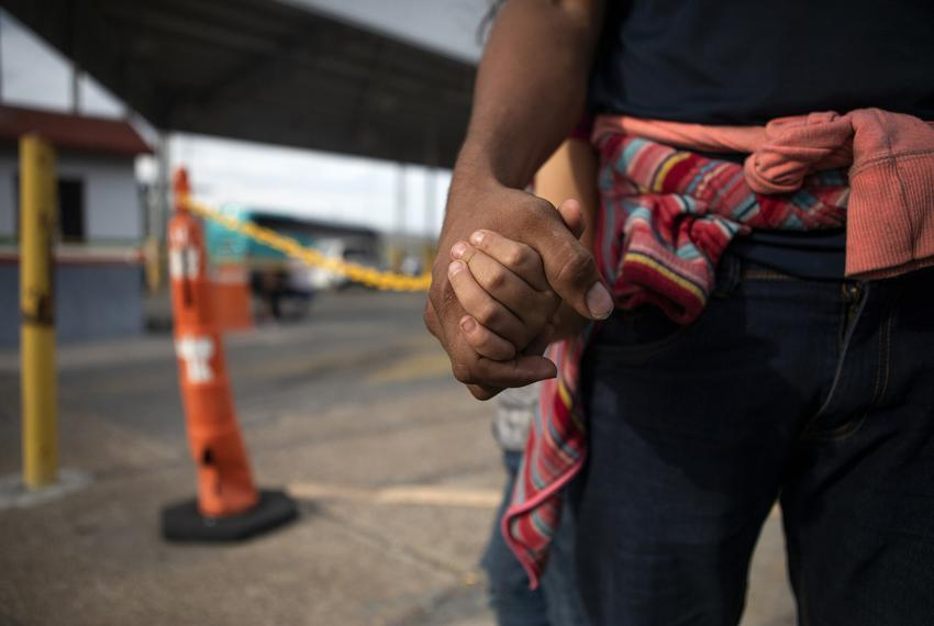 A Honduran migrant holds his daughters' hand at an immigration checkpoint in Nuevo Laredo. The pair requested asylum in th...