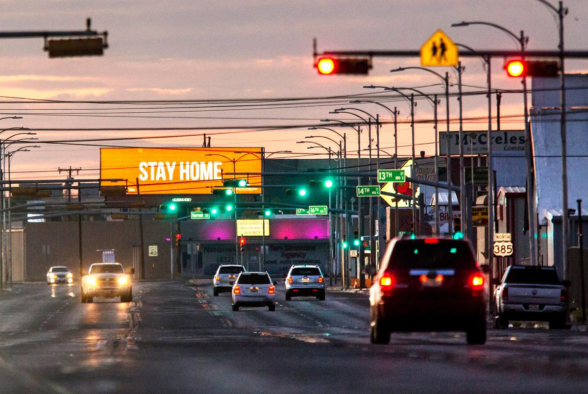 A handful of cars drive down Grant Avenue Thursday evening as an advertisement from Medical Center Hospital urges community members to stay home in Odessa on April 9, 2020.