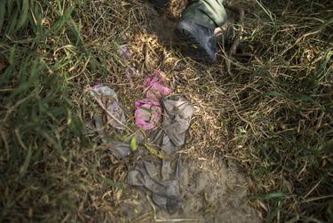 Border Patrol Agent Isaac Villegas steps over the discarded clothes of undocumented immigrants lining a footpath away from the Rio Grande riverbank in Roma, Texas. According to Border Patrol agents, undocumented immigrants crossing into South Texas from Mexico commonly change into a spare set of clothes after they cross the river to stand out less once inside the United States.