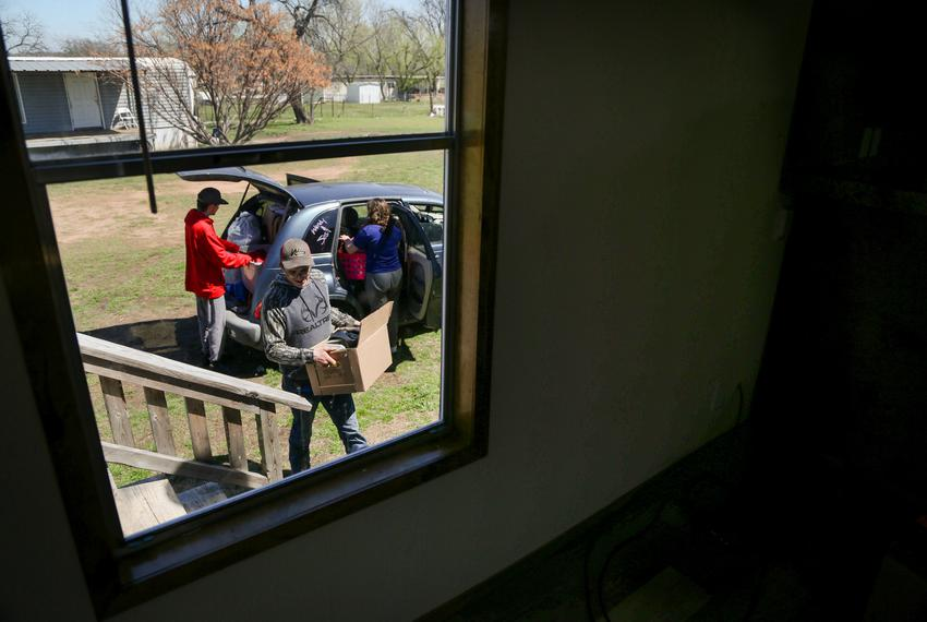Josh Short moves a box of belongings into their new mobile home while Peyton Sidex and Amanda Garrison unpack the family car…