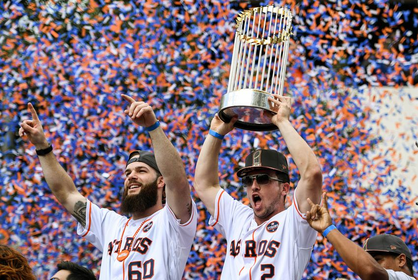 Houston Astros third baseman Alex Bregman lifts the trophy next to starting pitcher Dallas Keuchel during the World Series championship parade for the Houston Astros in downtown Houston on Nov. 3, 2017.