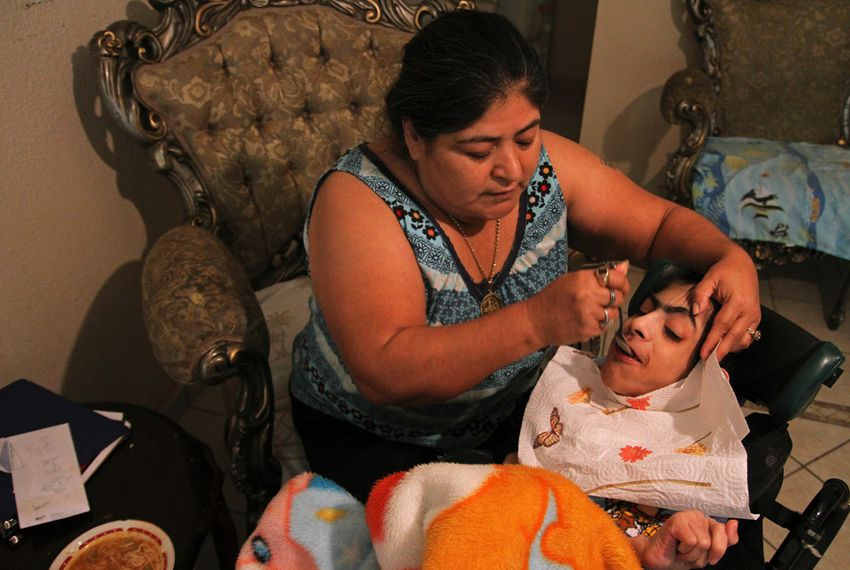 Maria Figueroa feeds Antonio Fuentes, 28, who has cerebral palsy and cannot speak. Figueroa has been Fuentes' health care provider for the past eight years.