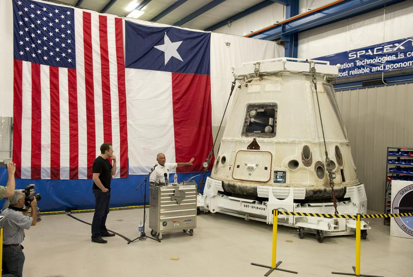 NASA administrator Charles Bolden, right, shows off the Dragon spacecraft as SpaceX CEO Elon Musk, left, listens in McGreg...