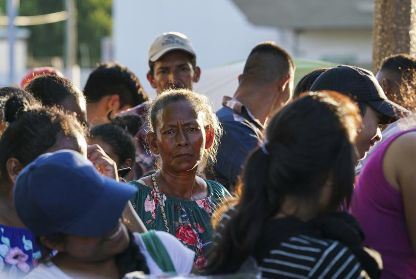 Asylum seekers wait in line to get a meal provided by Team Brownsville near the Gateway International Bridge in Matamoros, M…