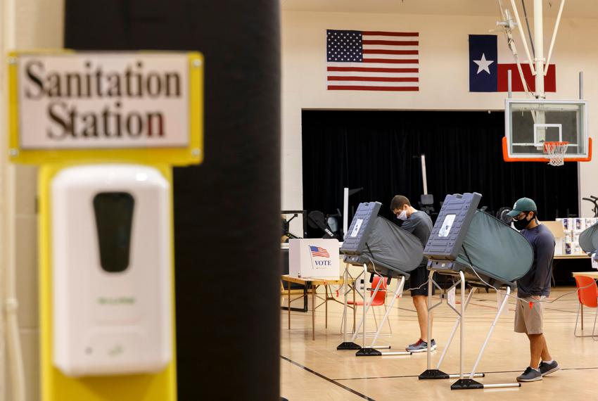 Voters cast ballots in booths spread six feet apart at the Metropolitan Multiservices Center for the delayed primary runof...