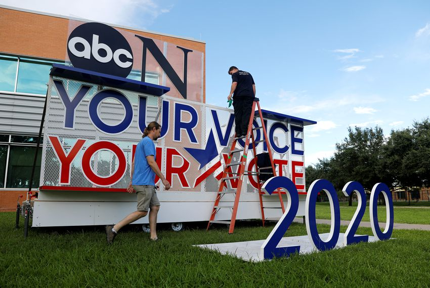 Works crews set up a sign as preparations continue for Thursday's Democratic presidential debate in Houston.