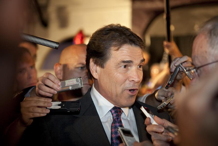 Gov. Rick Perry answers media questions upon his arrival at the Electric Park Ballroom in Waterloo, Iowa, on Aug. 14, 2011.
