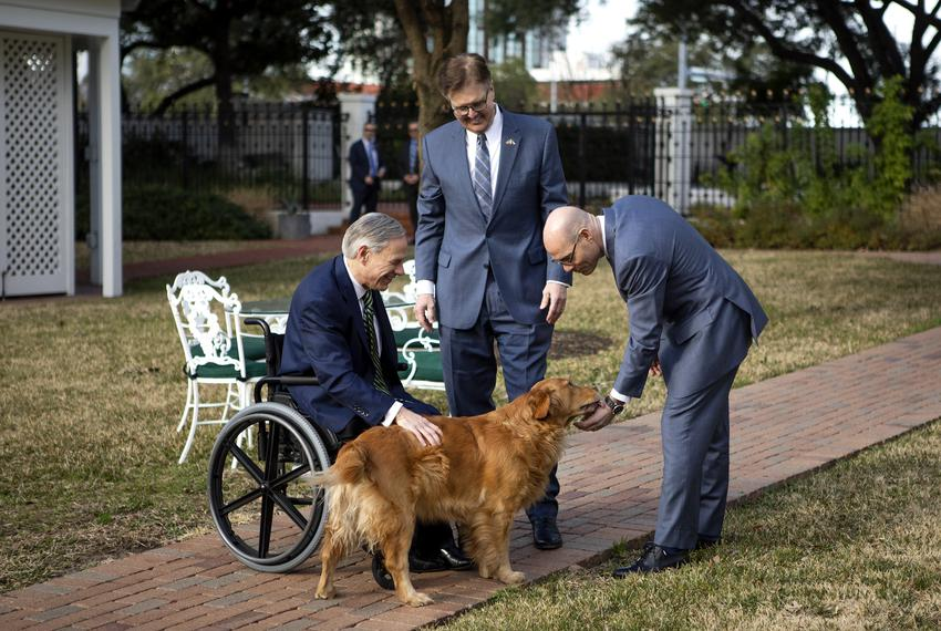 Governor Greg Abott, Lieutenant Governor Dan Patrick, and House Speaker Dennis Bonnen pet Pancake, the governor's dog after …