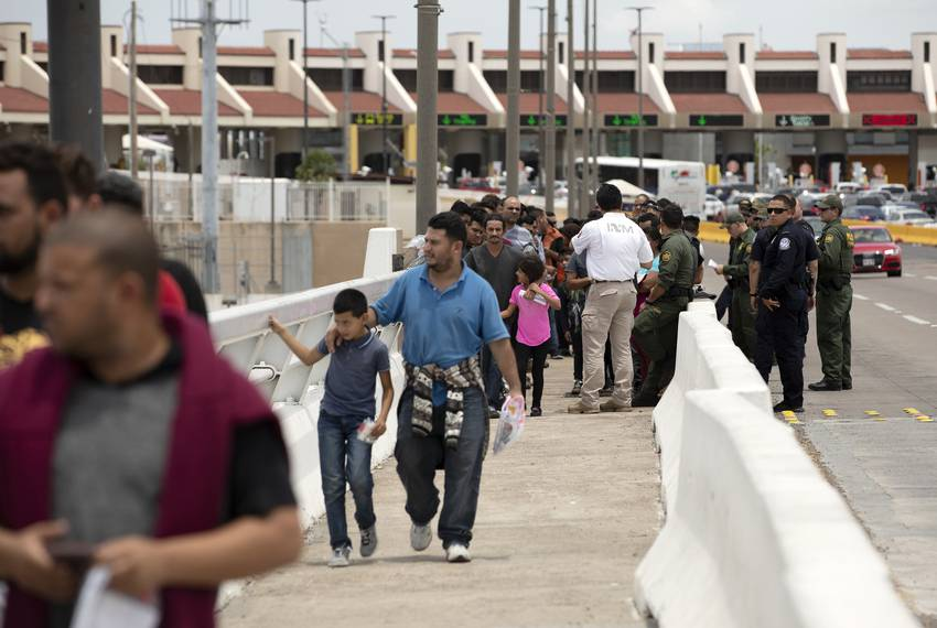 A group of migrants walk across Internation Bridge Two into Mexico from the United States. The group requested asylum in t...