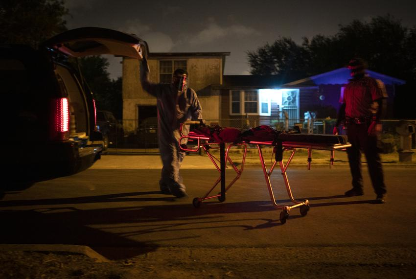 Juan Lopez wheels a stretcher out of the back of his vehicle in the early morning in McAllen. Lopez is picking up the body o…