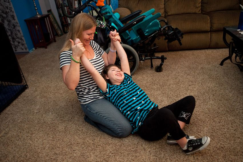 Milla and her mother, Cassie, do stretching exercises on the living room floor.