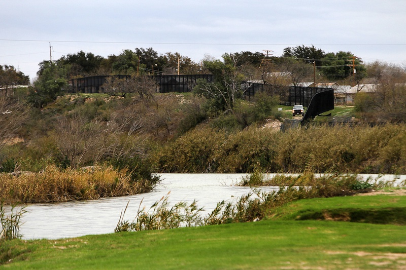 The Rio Grande and a towering border fence separate Eagle Pass, Texas from Piedras Negras, Mexico, Saturday, February 4, 2012.