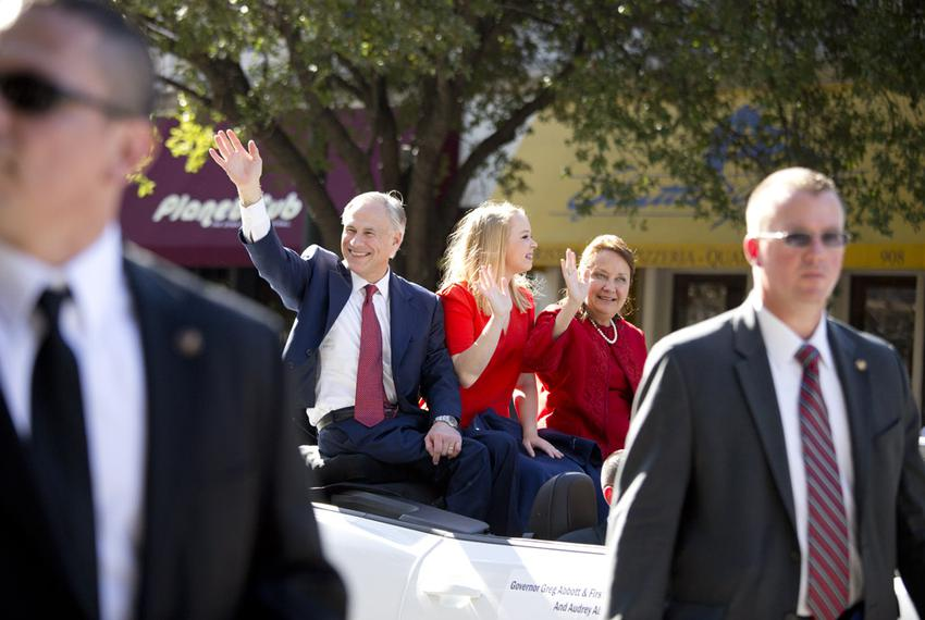 Flanked by security, Abbott and his family ride up Congress Avenue.