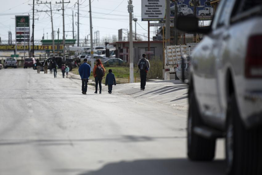 A small group of migrants walk down Libramiento Manuel Perez Trevino in Piedras Negras. The group had just left the migrant …