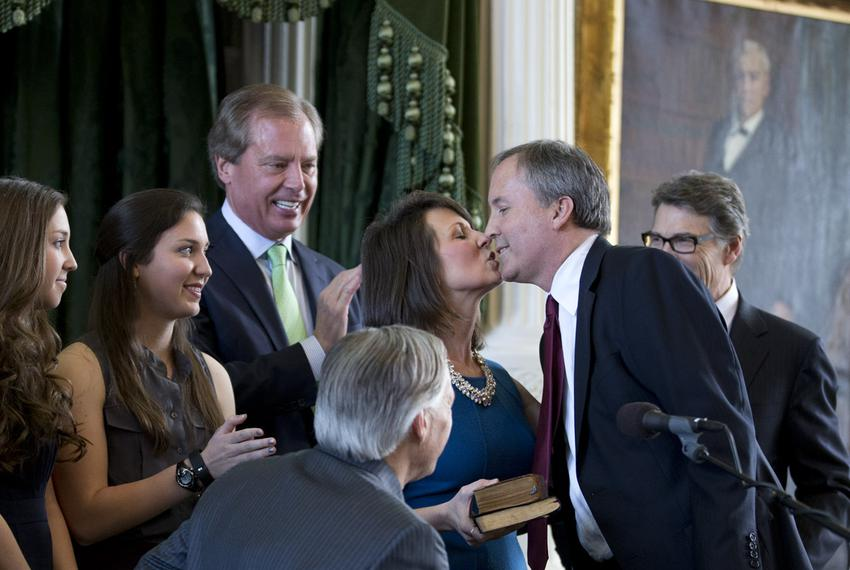Attorney General Ken Paxton gets a kiss from his wife, Angela, after he was sworn in on Jan. 5, 2015, in the Texas Senate ch…