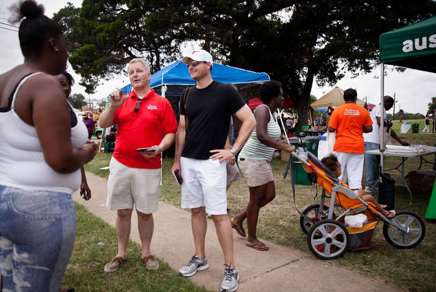 James Dickey, chairman of the Travis County Republican Party (in red), and Brendan Steinhauser, campaign manager for U.S. Sen. John Cornyn (in black), talked to members of the crowd at a Juneteenth celebration in East Austin on Saturday. Steinhauser's visit was part of the Cornyn campaign's efforts to reach diverse communities.