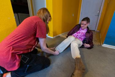 Susie Angel puts on her shoes with the help of her attendant Sandy White in her home in Austin on Jan. 30, 2019.