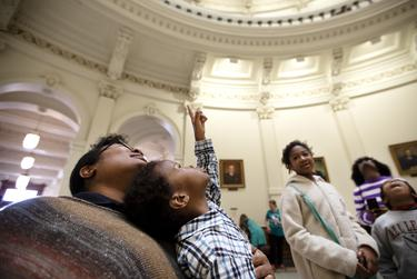 Chyrece Campbell holds Pierce Campbell as he looks up at the rotunda at the state capitol. Chyrece and her children, also pictured, Madison, Gregory and Kennedy, are visiting the capitol on the first day of the 86th legislative session. Miguel Gutierrez Jr.