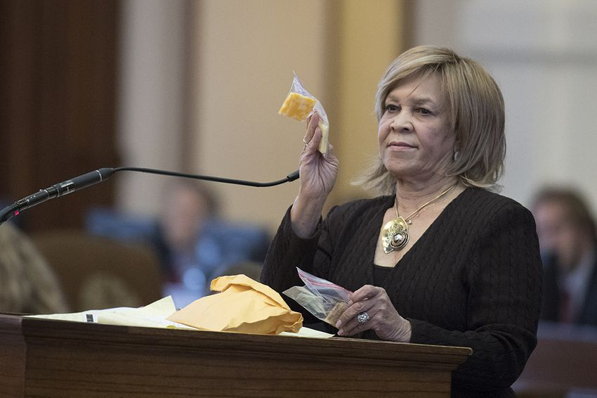 State Rep. Helen Giddings, D-Desoto, holds up a sample of a piece of cheese given to students who lack money to pay for school lunches in Dallas area schools during a personal privilege speech on the House floor May 9, 2017, where she chastised House Freedom Caucus members for killing her bill on school lunches for poor kids.