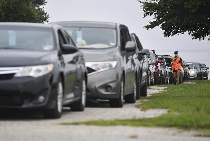 Cars line up for a drive-thru food distribution hosted by the Central Texas Food Bank at the Travis County Expo Center on Ju…