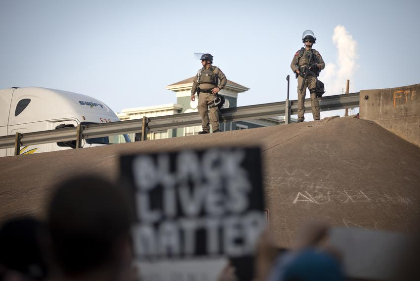State troopers stand near an overpass on Interstate 35 to prevent protesters from blocking traffic during a rally at Austin …