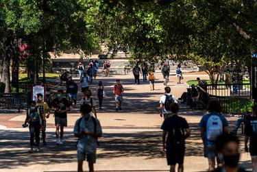 """Students walk through an area known as """"The Quad"""" on the first day of the fall semester at Texas State University in San Marcos on Aug. 24, 2020."""