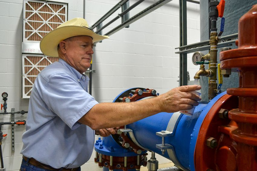 """Public Works Director Doug Hutcheson fills a cup with water at the water treatment plant in Wolfforth, Texas. """"We've tried to comply. We're team players. We're wanting to fix it and get it on down the road,"""" he said."""
