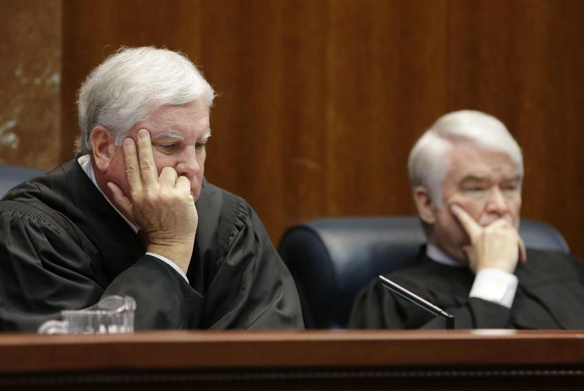 Texas Supreme Court Justices Paul Green, left, and Chief Justice Nathan Hecht listen to oral arguments Sept. 1 in Texas' app…