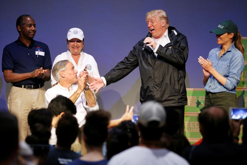 From left, Gov. Greg Abbott reacts as President Donald Trump speaks at a church relief center during a visit with flood su...