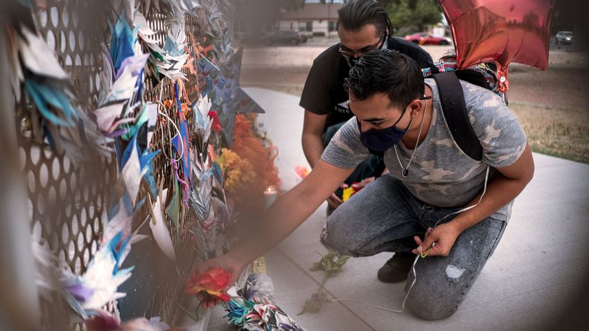Isaiah Vale  places flowers at a memorial honoring the victims of the Walmart shooting at Ponder Park in El Paso.