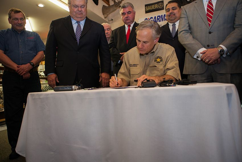 Gov. Greg Abbott signs an open-carry bill passed by the state Legislature at Red's Indoor Range, a gun store and shooting range in Pflugerville, Texas, on June 13, 2015.