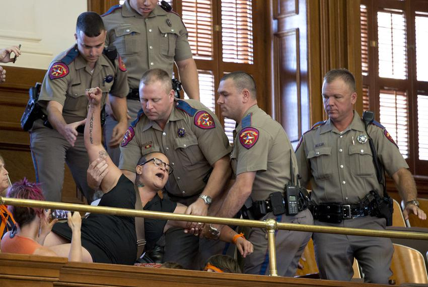 A protester who yelled out during the final vote on HB 2 the abortion bill is removed from the House gallery on July 10, 201…