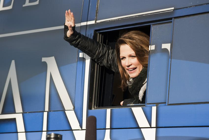 Republican candidate Michele Bachmann waves to reporters from her bus after leaving the Rock the Caucus event at Valley High…