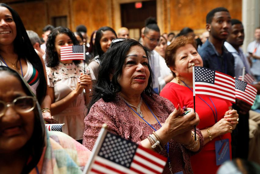 New citizens stand during a U.S. Citizenship and Immigration Services (USCIS) naturalization ceremony at the New York Public…