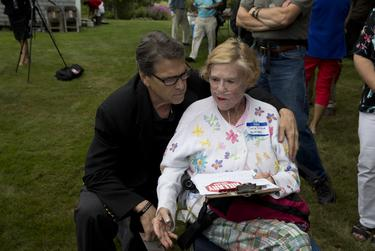Gilford, N.H. activist Joyce Fitkin visits with Gov. Rick Perry at the Merrimack County GOP picnic on Saturday.