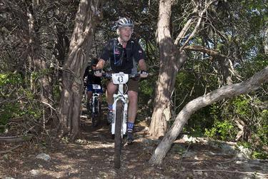 Former President Bush leads the way through a stand of cedar trees on his ranch near Crawford during his annual W100K ride for wounded veterans on May 1, 2015.