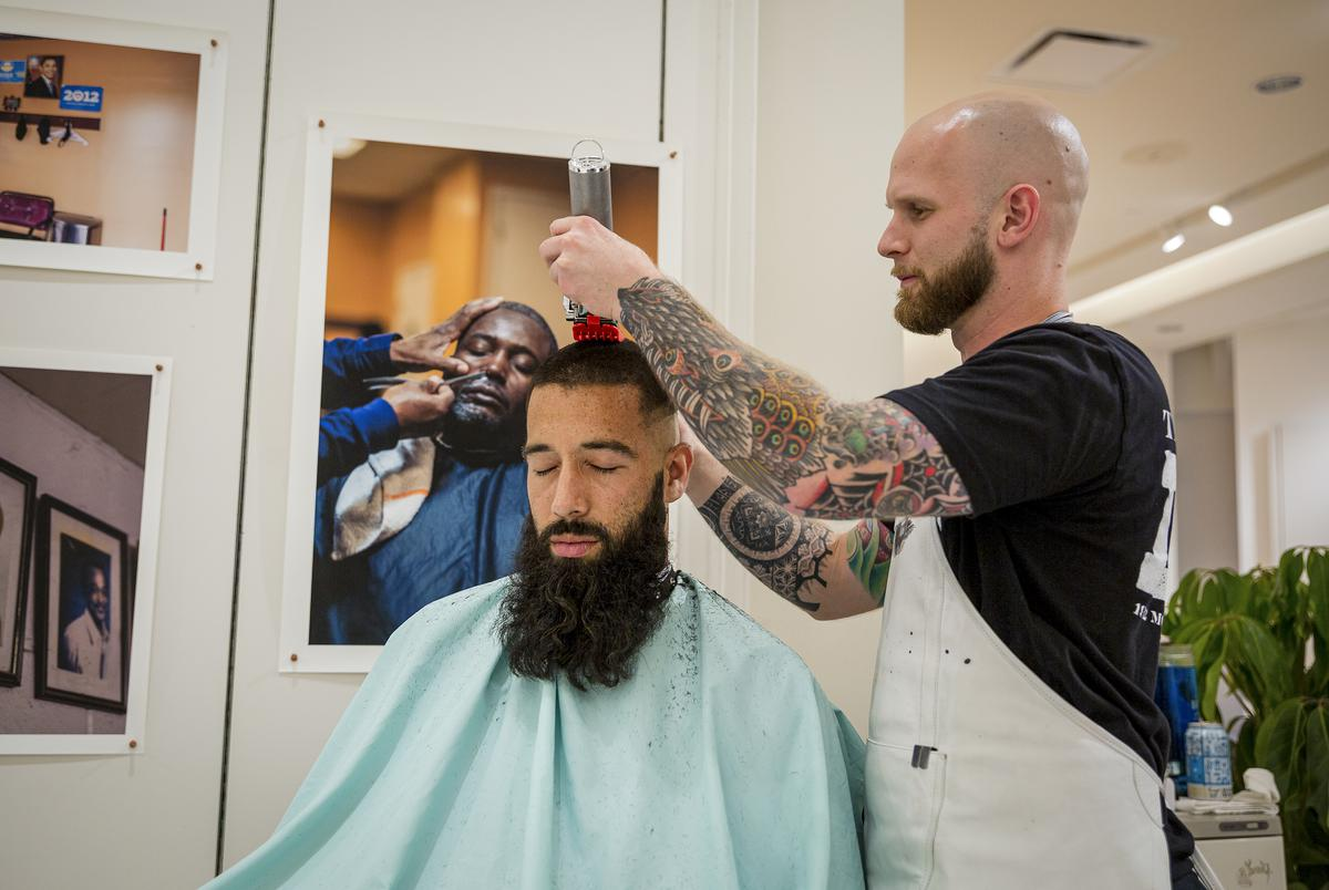 Daniel Adell cuts Troy Montes's hair as a performance component of Montes's work 'Thairapy' during the From Houston, With Love Art Exhibition preview in Downtown Houston on June 13, 2021. Troy Montes identifies as Latino and uses masculine pronouns. Daniel Adell identifies as white and uses masculine pronouns.