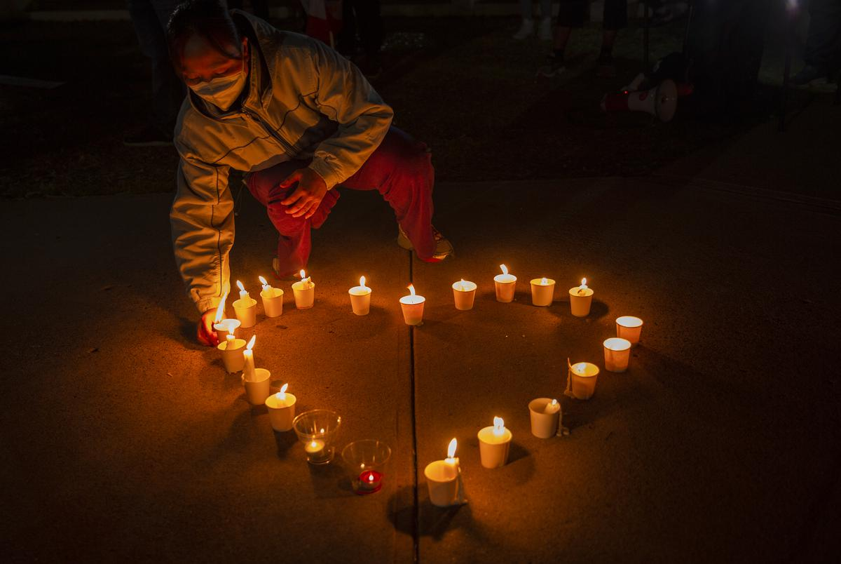 Qiongxia Lin prepares candles in a heart shape at the Grassy Knoll in Dallas to honor to the victims of the shootings in Atlanta.