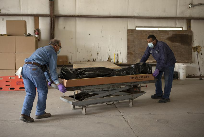 From left, Al Luna and Miguel Guzman move the body of someone that recently died from COVID-19 onto a table. They will sho...